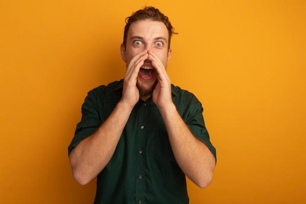 Podekscytowany przystojny blondyn trzyma ręce blisko ust na białym tle na pomarańczowej ścianie