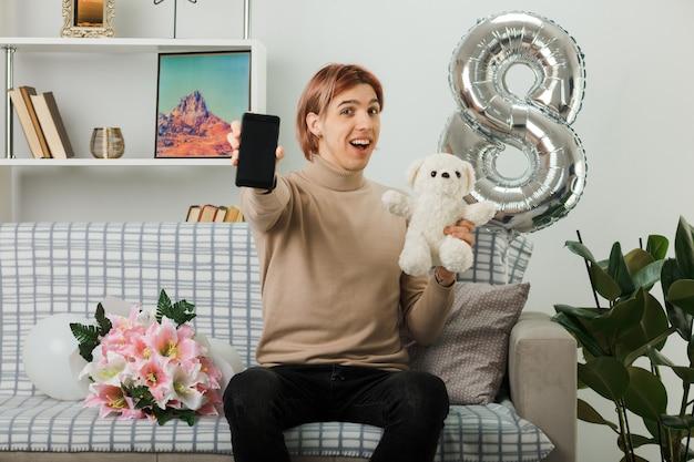 Podekscytowany przystojny facet na szczęśliwy dzień kobiet trzymający misia z telefonem siedzącym na kanapie w salonie