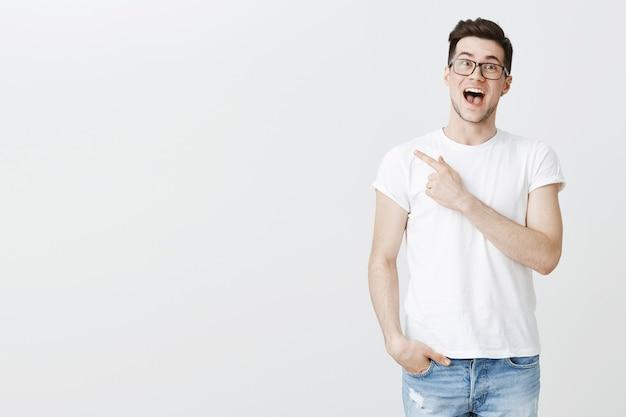 Podekscytowany przystojny facet udostępnia link, wskazując palcem w lewo zdumiony