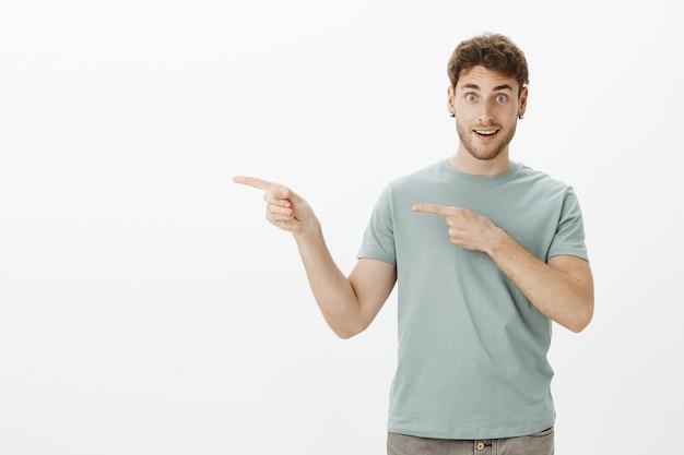 Podekscytowany przystojny facet w kolczykach i koszulce, wskazujący w lewo palcami wskazującymi i szeroko uśmiechnięty, pytający, czy przyjaciele chcą z nim iść