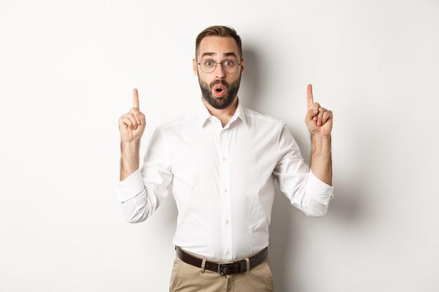Podekscytowany przystojny facet w okularach, wskazując palcami w górę, pokazując baner informacyjny, stojąc na białym tle. skopiuj miejsce