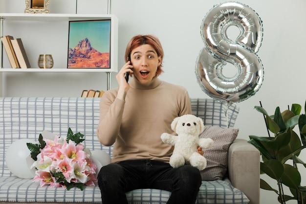 Podekscytowany przystojny facet w szczęśliwy dzień kobiet trzymający pluszowego misia rozmawia przez telefon, siedząc na kanapie w salonie