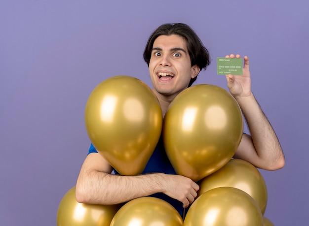 Podekscytowany przystojny kaukaski mężczyzna stoi z balonami z helem, trzymając kartę kredytową