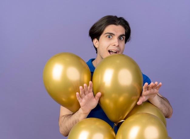 Podekscytowany przystojny kaukaski mężczyzna stoi z balonami z helem wyciągniętymi rękami