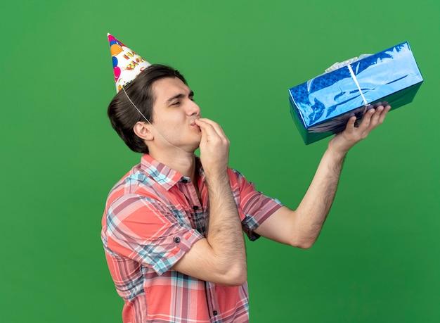 Podekscytowany przystojny kaukaski mężczyzna w czapce urodzinowej stoi bokiem, trzymając i patrząc na pudełko, gestykulując pyszny znak