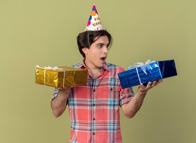 Podekscytowany przystojny kaukaski mężczyzna w czapce urodzinowej trzyma i patrzy na pudełka z prezentami