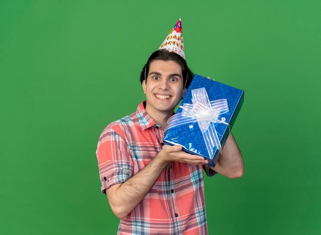 Podekscytowany przystojny kaukaski mężczyzna w czapce urodzinowej trzyma pudełko na prezent