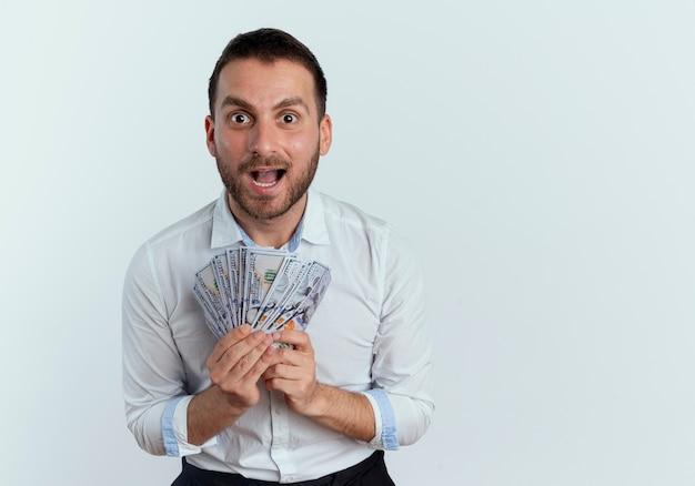 Podekscytowany przystojny mężczyzna trzyma pieniądze na białym tle na białej ścianie