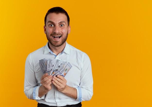 Podekscytowany przystojny mężczyzna trzyma pieniądze, patrząc na białym tle na pomarańczowej ścianie