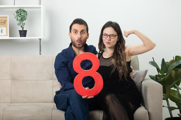 Podekscytowany przystojny mężczyzna trzymający czerwoną ósemkę i ładną młodą kobietę w okularach optycznych napinającą bicepsy, siedzącą na kanapie w salonie w marcowy międzynarodowy dzień kobiet