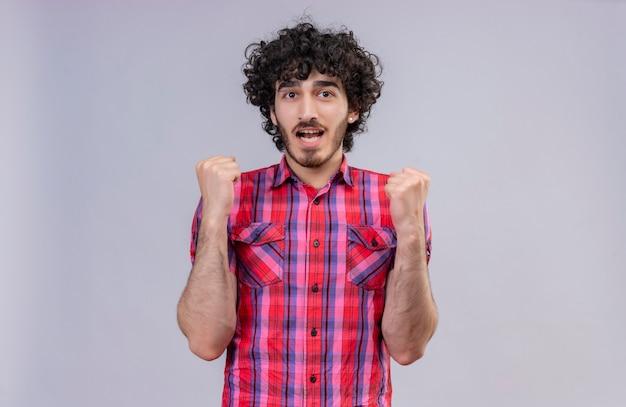 Podekscytowany przystojny mężczyzna z kręconymi włosami w koszuli w kratę unoszący zaciśnięte pięści