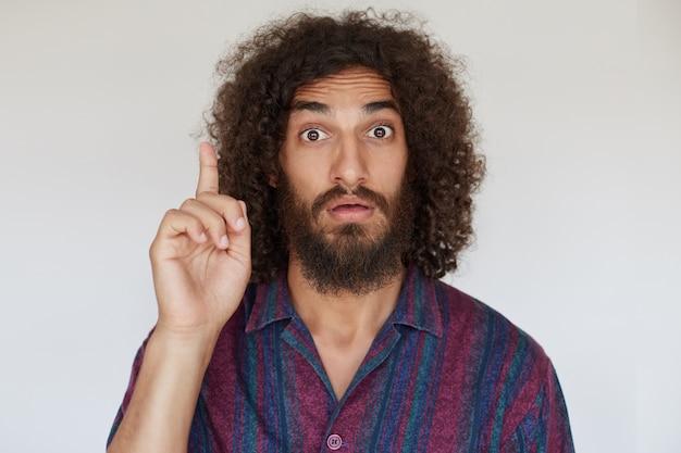 Podekscytowany przystojny młody ciemnowłosy, kręcony mężczyzna z brodą unoszącą palec wskazujący, jak ma dobry pomysł, marszczące czoło z szeroko otwartymi oczami