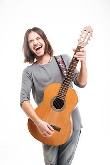 Podekscytowany przystojny młody mężczyzna z długimi włosami, śmiejący się i grający na gitarze akustycznej na białym tle