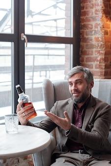 Podekscytowany przystojny siwy mężczyzna siedzi w luksusowym fotelu i poleca znajomemu whisky
