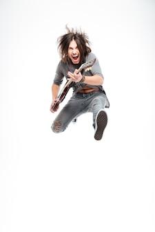 Podekscytowany, radosny młody gitarzysta z gitarą elektryczną krzyczącą i skacząc nad białym tłem