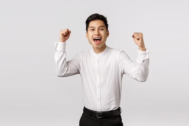 Podekscytowany, radujący się młody azjatycki odnoszący sukcesy biznesmen świętuje zwycięstwo, zostaje mistrzem, osiąga cel, pompuje pięści i krzyczy tak, jak się czuje zadowolony, drużyna wygrała, raduje się ze zwycięstwa,