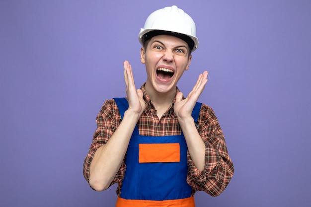Podekscytowany rękami wokół twarzy młodego budowniczego płci męskiej w mundurze