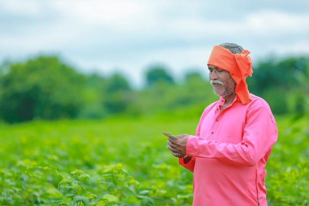 Podekscytowany rolnik z banknotami rupii indyjskiej