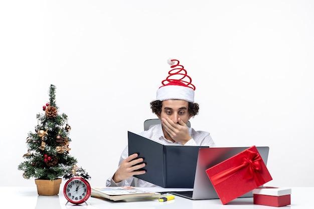 Podekscytowany smutny młody biznesmen z zabawnym czapką świętego mikołaja sprawdzanie informacji w dokumentach w biurze na białym tle