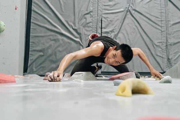 Podekscytowany, spocony, sprawny mężczyzna wspinający się po boulderingwall, widok z góry