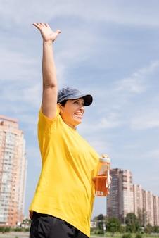 Podekscytowany starszy kobieta wita wodę pitną po treningu na świeżym powietrzu na boisku sportowym