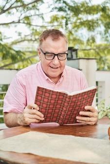 Podekscytowany starszy mężczyzna w okularach czytający urzekającą książkę, siedząc przy stole w kawiarni na świeżym powietrzu