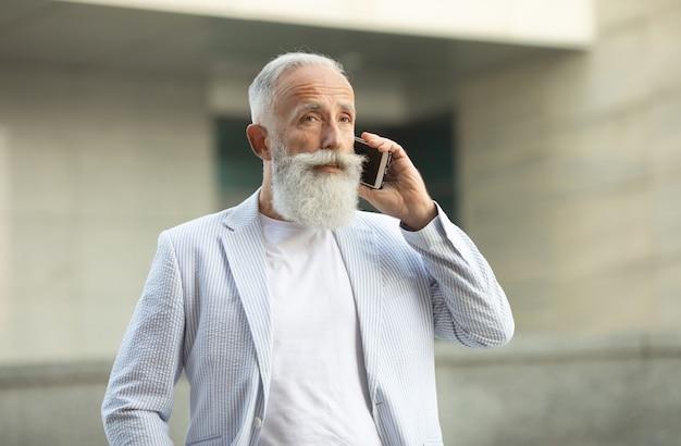 Podekscytowany starzec w kurtce z siwymi włosami i brodą rozmawia przez telefon