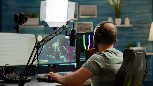 Podekscytowany streamer ze słuchawkami wygrywający ważne zawody e-sportowe online w kosmicznej strzelance grającej na potężnym komputerze. profesjonalne strumieniowe przesyłanie gier wideo dla profesjonalnych graczy za pomocą profesjonalnego mikrofonu i