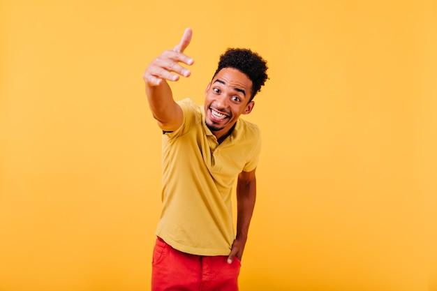 Podekscytowany stylowy mężczyzna z krótkimi włosami macha ręką. kryty portret pozytywnego śmiechu afrykańskiego faceta.
