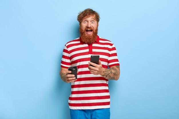 Podekscytowany stylowy rudy facet pozuje na niebieskiej ścianie