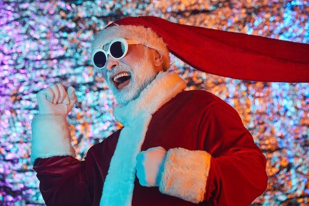 Podekscytowany święty mikołaj w okularach przeciwsłonecznych, zabawy podczas imprezy