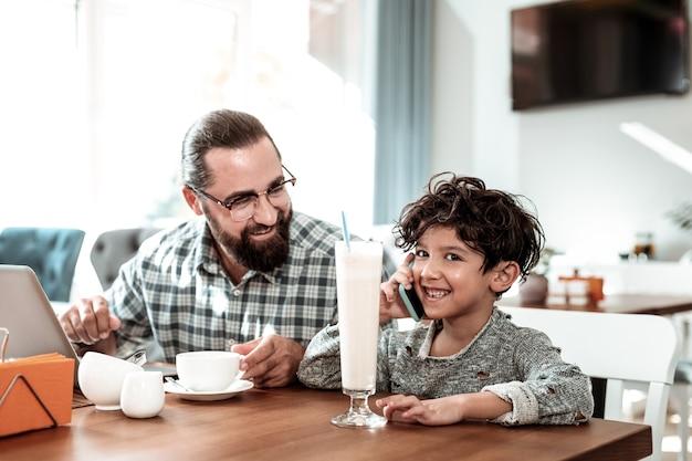 Podekscytowany syn. ciemnowłosy uroczy syn czuje się szczęśliwy i podekscytowany rozmawiając przez telefon z matką