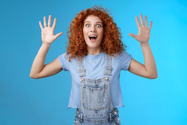 Podekscytowany szalony zabawny zabawny rudowłosy kędzierzawy wzruszający dziewczyna krzyczy beztroski podnoszenie rąk poddaje się otwartym ustom wygłupia się uśmiechając się szeroko gapi aparat radosny wyraża dzikie śmiałe emocje.
