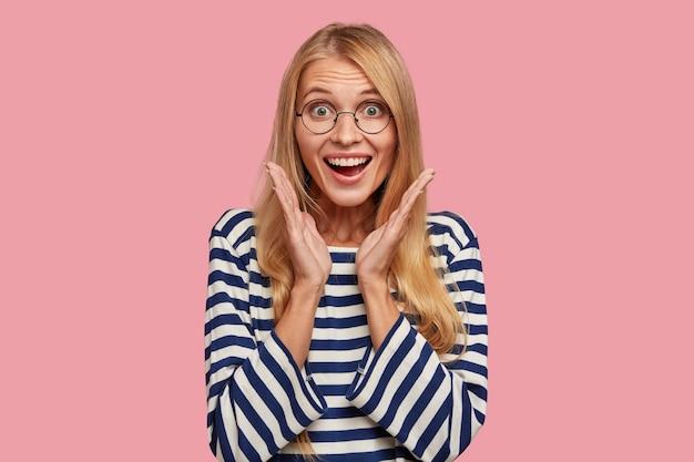 Podekscytowany szczęśliwy blond kobieta pozuje na różowej ścianie
