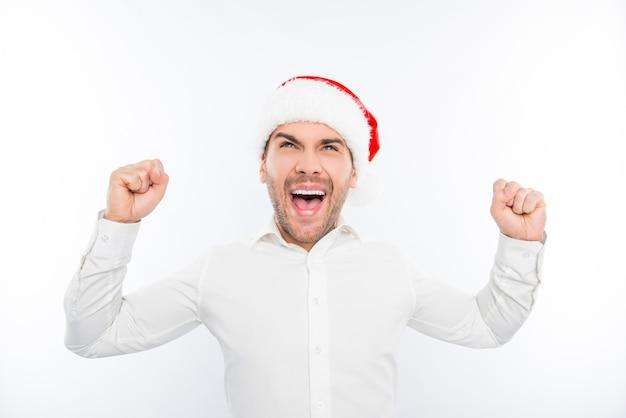Podekscytowany szczęśliwy człowiek w czapce mikołaja świętuje nowy rok i triumfuje