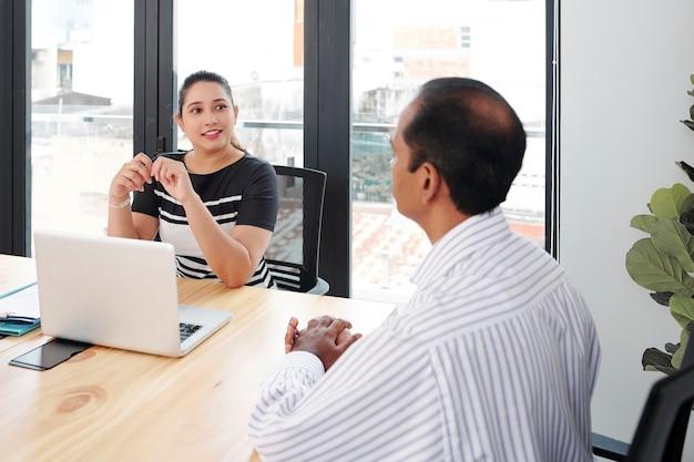 Podekscytowany szczęśliwy indyjski bizneswoman siedzi przy stole z otwartym laptopem i prowadzi rozmowę kwalifikacyjną z kandydatem