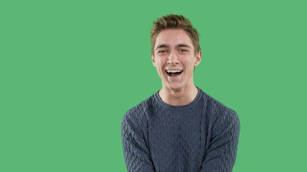 Podekscytowany szczęśliwy młody chłopak, koncepcja powodzenia na zielonym tle