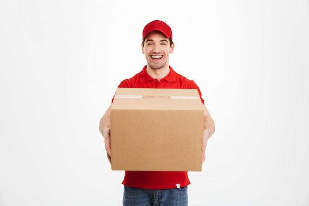 Podekscytowany szczęśliwy młody człowiek dostawy w czerwonej czapce