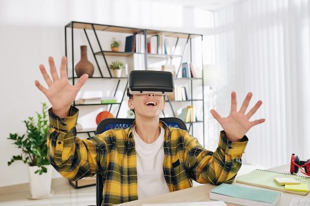 Podekscytowany szczęśliwy nastoletni chłopak grając w gry w zestawie słuchawkowym wirtualnej rzeczywistości, siedząc przy tablecie