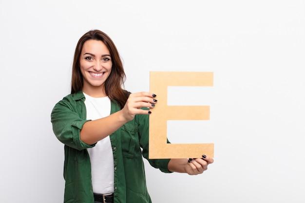 Podekscytowany, szczęśliwy, radosny, trzymając literę e alfabetu, aby utworzyć słowo lub zdanie.