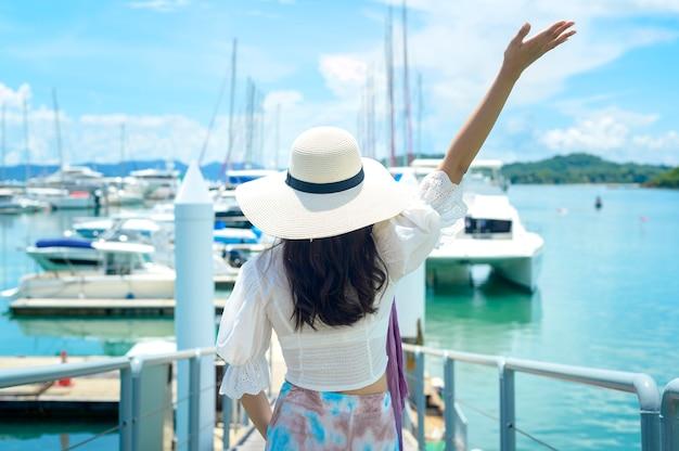 Podekscytowany turysta w białym kapeluszu, cieszący się i stojący na doku z luksusowymi jachtami latem