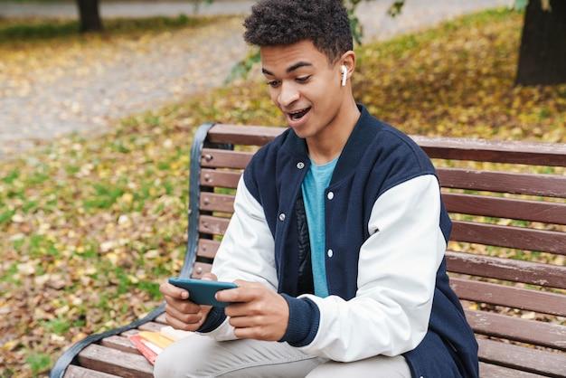 Podekscytowany uczeń chłopiec siedzi na ławce w parku, grając w gry na telefonie komórkowym