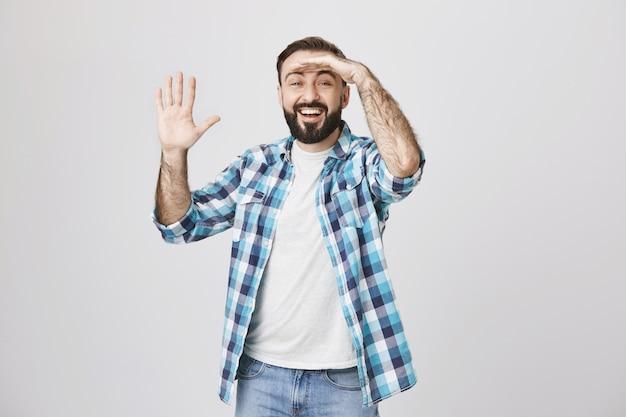 Podekscytowany uśmiechnięty mężczyzna patrzy w dal, wita kogoś, macha ręką na przywitanie