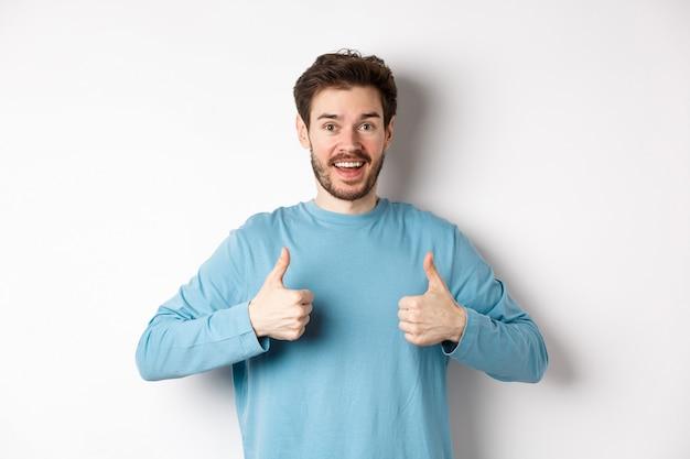 Podekscytowany uśmiechnięty mężczyzna pokazujący kciuki do góry, by pochwalić doskonały produkt, wyglądający na zdumionego i szczęśliwego w aparacie, polecający dobrą ofertę, stojący na białym tle