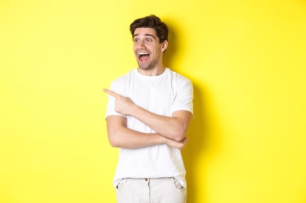 Podekscytowany uśmiechnięty mężczyzna wskazujący i patrząc w lewo, sprawdzający ofertę promocyjną, stojący na żółtym tle.