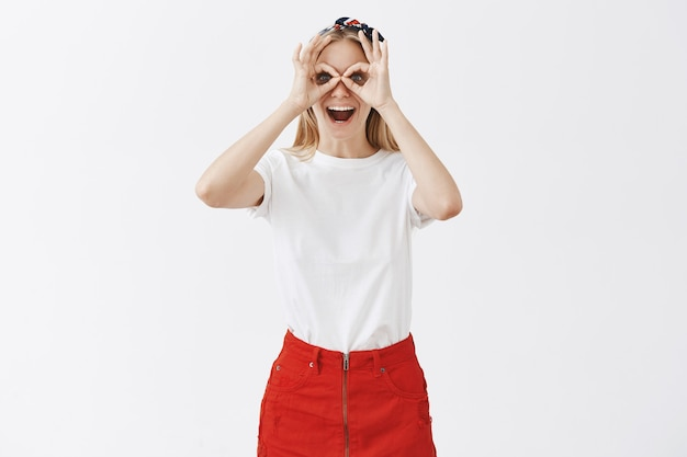 Podekscytowany wesoła młoda blond dziewczyna pozuje na białej ścianie