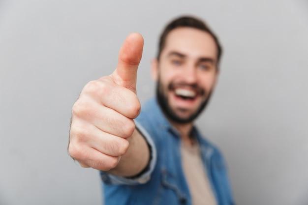 Podekscytowany wesoły mężczyzna ubrany w koszulę na białym tle nad szarą ścianą, pokazując kciuki do góry