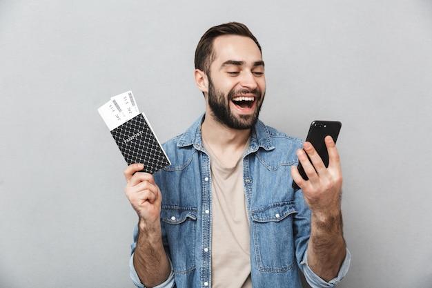 Podekscytowany wesoły mężczyzna ubrany w koszulę na białym tle nad szarą ścianą, trzymając paszport z biletami lotniczymi, przy użyciu telefonu komórkowego