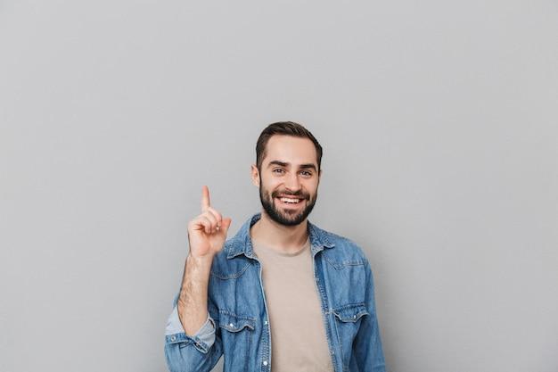 Podekscytowany wesoły mężczyzna ubrany w koszulę na białym tle nad szarą ścianą, wskazując na miejsce