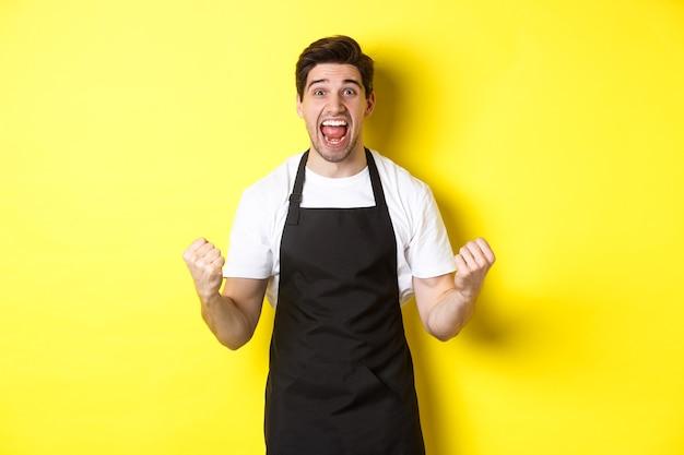 Podekscytowany właściciel kawiarni w czarnym fartuchu świętuje, pompuje pięścią i krzyczy z radości, osiąga cel, stoi przed żółtą ścianą